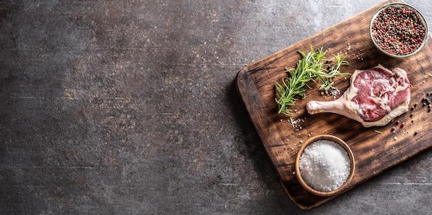Widok z góry rustykalna drewniana deska do krojenia z udem kaczki, ziołami, przyprawami i solą, pokrywająca połowę metalicznego tła.