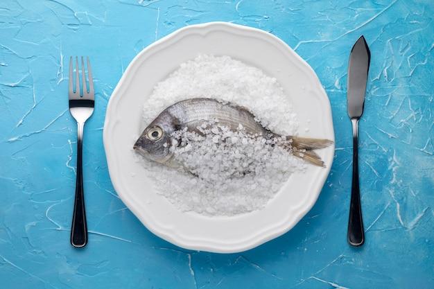 Widok z góry ryby na talerzu z solą i sztućcami