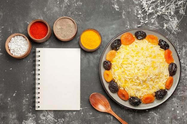 Widok z góry ryż ryżowy z suszonymi owocami łyżka przyprawy notatnik