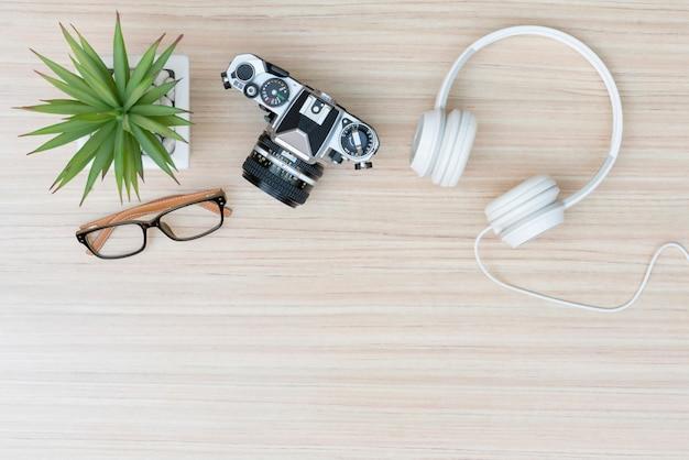 Widok z góry rzeczy podróżniczych. aparat, słuchawki i okulary na drewnianym stole z miejsca na kopię