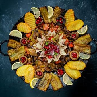 Widok z góry saj z jagnięciną i wołowiną na talerzu o czarnym teksturowanym tle