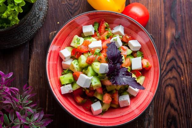 Widok z góry sałata grecka, pomidory, ser feta, ogórki, czarne oliwki, fioletowa cebula