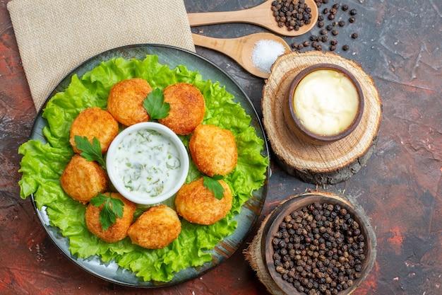 Widok z góry sałata z kurczaka na talerzu sól i czarny pieprz w drewnianych łyżkach sos i czarny pieprz w miskach na ciemnym stole