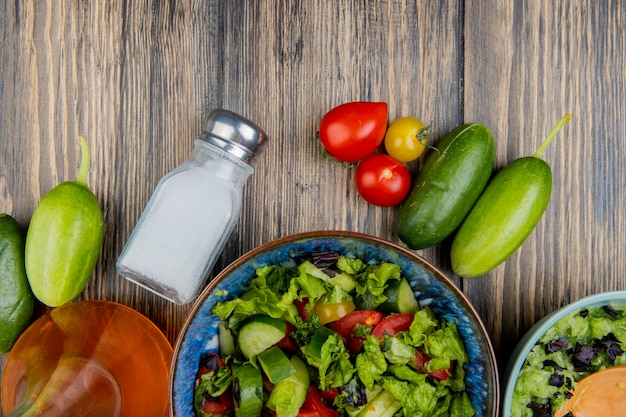 Widok z góry sałatek warzywnych z ogórkiem pomidorowym stopionym olejem i solą na drewnie