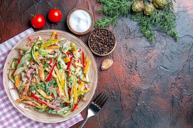 Widok z góry sałatka jarzynowa na talerzu na obrusie widelec sól i czarny pieprz pomidory gałązki sosny na ciemnoczerwonym stole wolne miejsce
