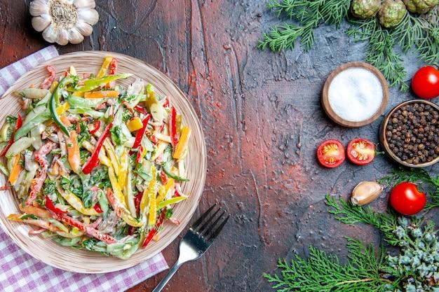 Widok z góry sałatka jarzynowa na talerzu obrus widelec sól i czarny pieprz pomidory czosnkowe na ciemnoczerwonym stole