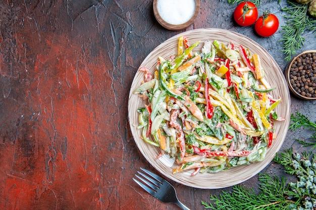Widok z góry sałatka jarzynowa na talerzu widelec pomidory sól czarny pieprz gałęzie sosny na ciemnoczerwonym stole kopia przestrzeń