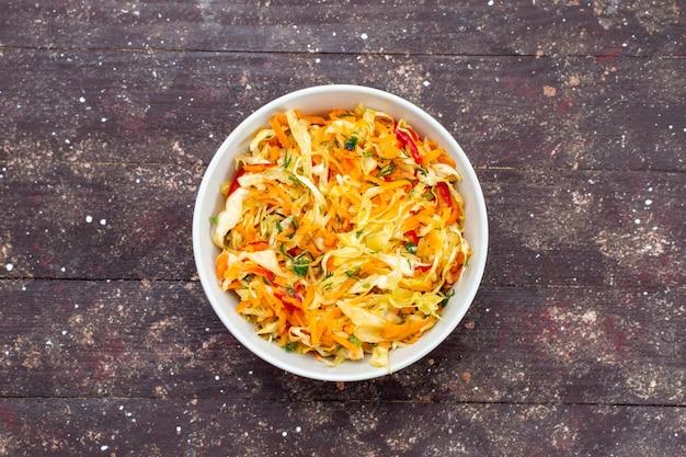 Widok z góry sałatka jarzynowa w plasterkach świeże i solone wewnątrz płyty na brązowym tle potrawa mączka warzywna danie świeże zdjęcie