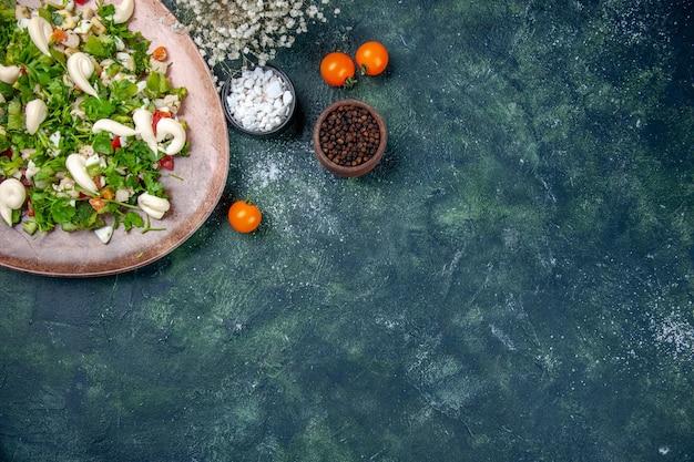 Widok z góry sałatka jarzynowa wewnątrz elegancki talerz ze sztućcami na ciemnoniebieskim tle kuchnia obiad zdrowie dieta kolor kuchnia obiad pasuje do restauracji posiłek wolna przestrzeń
