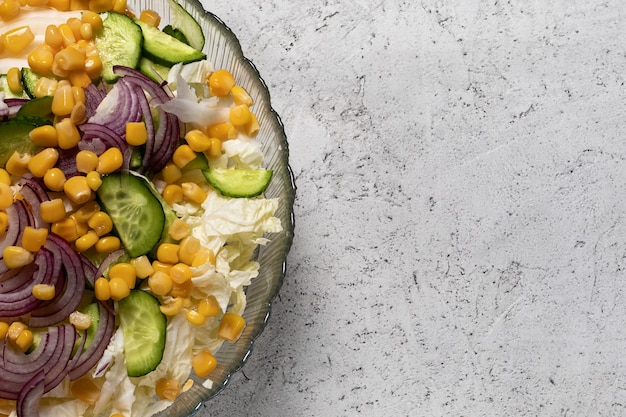 Widok z góry sałatka jarzynowa z kapustą pekińską, ziarnami kukurydzy cukrowej, pokrojoną cebulą i ogórkiem w szklanej misce na betonowym tle, miejsce po prawej stronie. pojęcie zdrowej i wegańskiej żywności.