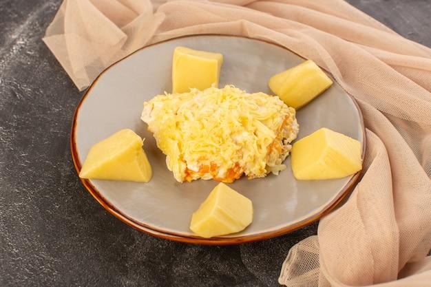 Widok z góry sałatka jarzynowa z majonezem, kurczakiem w środku i świeżym serem w talerzu na szarym biurku danie z sałatką