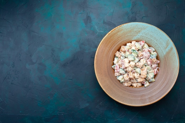 Widok z góry sałatka majonezowa pokrojone warzywa wewnątrz płyty na ciemnoniebieskim tle posiłek przekąska kolor zdjęcie