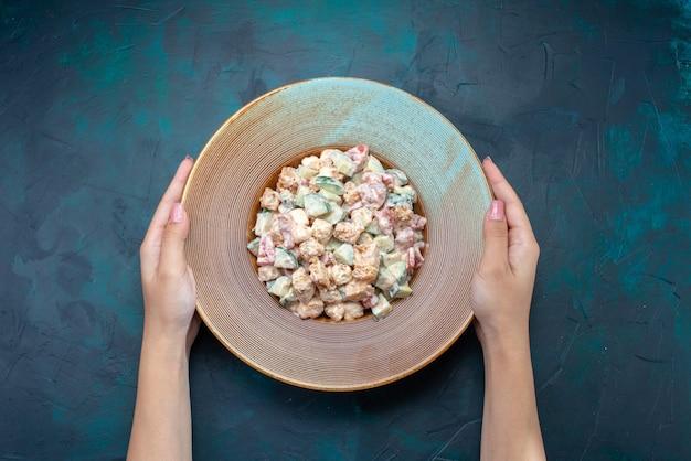 Widok z góry sałatka majonezowa pokrojone warzywa wewnątrz talerza na ciemnoniebieskim biurku posiłek warzywny kolor obiadowy