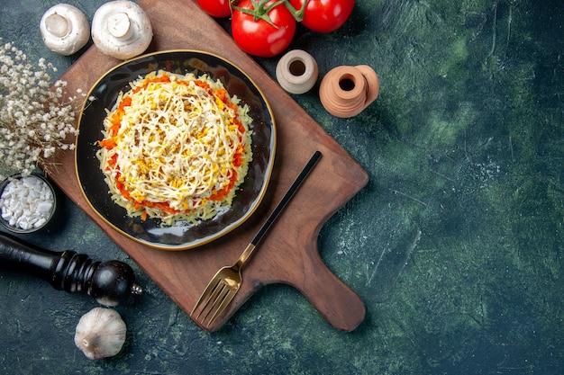 Widok z góry sałatka mimozy wewnątrz płyty z pieczarkami i pomidorami na ciemnym niebieskim tle