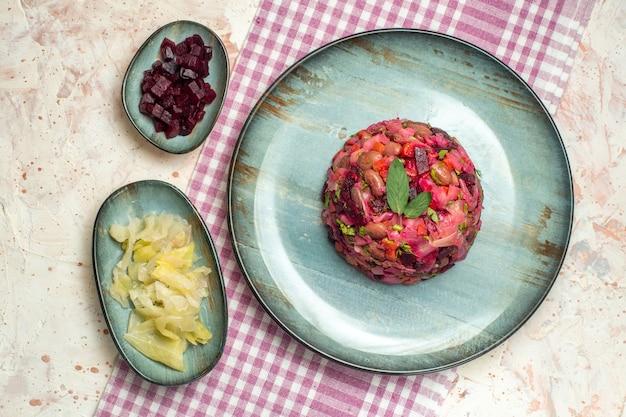 Widok z góry sałatka vinaigrette na owalnym talerzu pokrojone buraki i inne rzeczy w miskach na fioletowym białym obrusie w kratkę na jasnoszarym stole