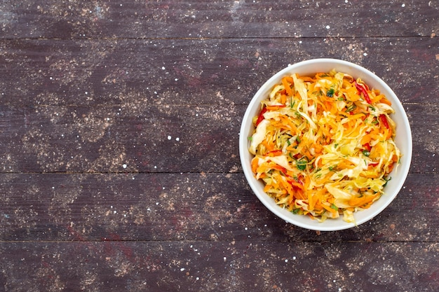 Widok z góry sałatka warzywna w plasterkach świeże i solone wewnątrz płyty na brązowym biurku danie z warzywami posiłek świeże zdjęcie
