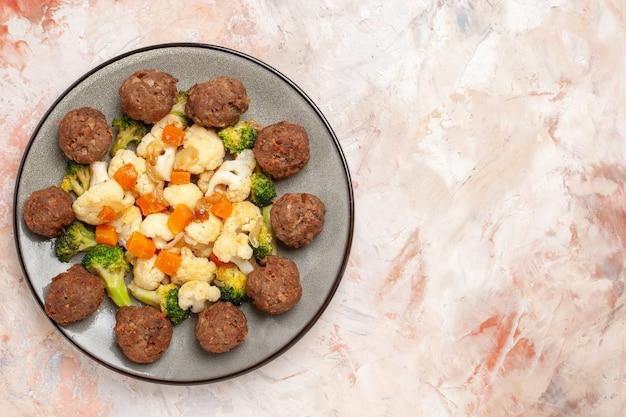 Widok z góry sałatka z brokułów i kalafiora i klopsiki na talerzu na nagiej powierzchni na białym tle z miejsca na kopię