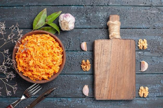 Widok z góry sałatka z tartej marchewki z czosnkiem i orzechami włoskimi na ciemnym rustykalnym biurku zdrowa dieta warzywna sałatka kolor dojrzały