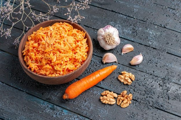Widok z góry sałatka z tartej marchewki z czosnkiem wewnątrz talerza na ciemnoniebieskim rustykalnym biurku sałatka zdrowotna dojrzała dieta w kolorze warzyw
