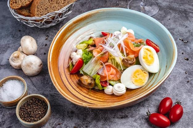 Widok z góry sałatką z wędzonego łososia z gotowaną jajkiem, pomidorową sałatą, grzybową cebulą