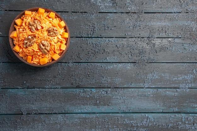 Widok z góry sałatka ze świeżej marchewki tarta sałatka z orzechami włoskimi i czosnkiem na ciemnym biurku dieta zdrowotna pomarańczowa dojrzała kolorowa sałatka