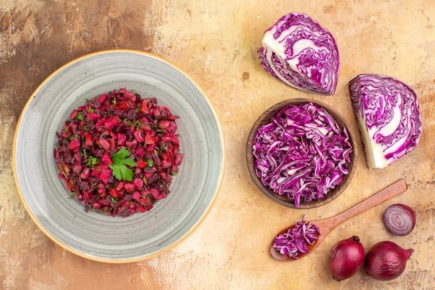 Widok z góry sałatka ze świeżych warzyw na talerzu ceramicznym z miski posiekanej czerwonej kapusty i czerwonej cebuli na drewnianym tle