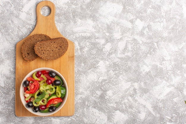 Widok z góry sałatka ze świeżych warzyw z pokrojonymi ogórkami, pomidorami, oliwą i białym serem wewnątrz talerza z chlebem na szarym tle