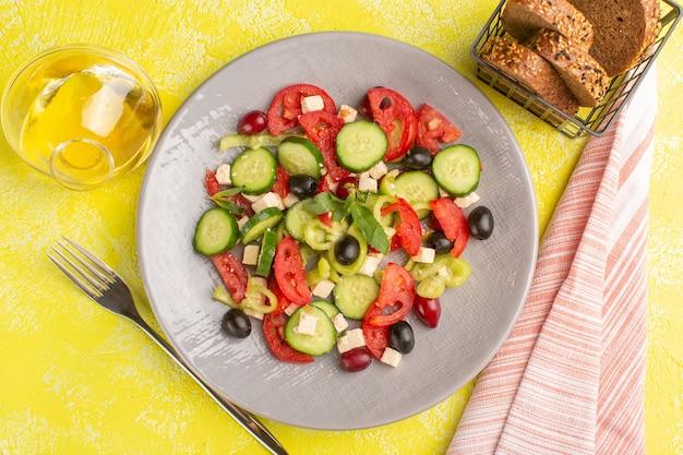 Widok z góry sałatka ze świeżych warzyw z pokrojonymi w plasterki ogórkami pomidory oliwka wewnątrz płyty z olejem i chlebem na żółtej powierzchni kolor sałatki warzywnej