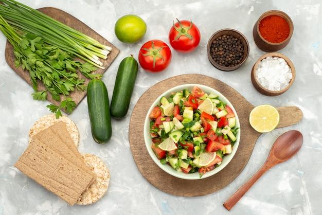 Widok z góry sałatka ze świeżych warzyw z pokrojonymi warzywami i plasterkami cytryny wewnątrz okrągłego talerza z chipsami na niebiesko