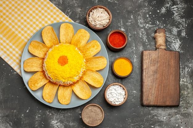 Widok z góry sałatki po lewej stronie, a pod nią żółta serwetka z deską do krojenia ziół na ciemnoszarym stole