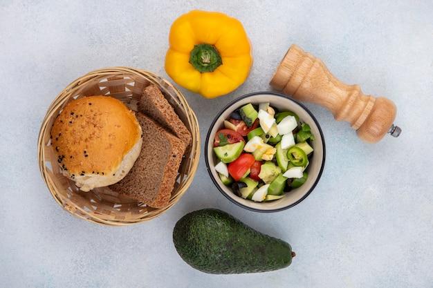 Widok z góry sałatki warzywnej, w tym papryki pomidorowo-ogórkowej w misce z wiadrem chleba żółtej papryki i awokado na białej powierzchni
