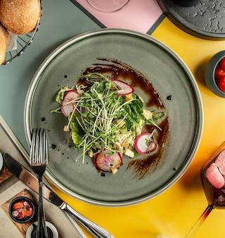 Widok z góry sałatki z awokado z rzodkiewką, żółtą papryką i świeżymi ziołami