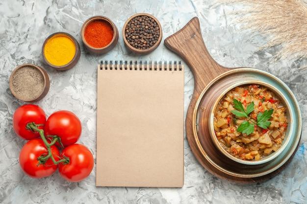 Widok z góry sałatki z pieczonego bakłażana w misce na desce do krojenia różne przyprawy w miskach pomidory notebook na szarej powierzchni