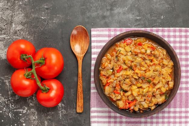 Widok z góry sałatki z pieczonego bakłażana w misce pomidory drewnianą łyżką na ciemnej powierzchni