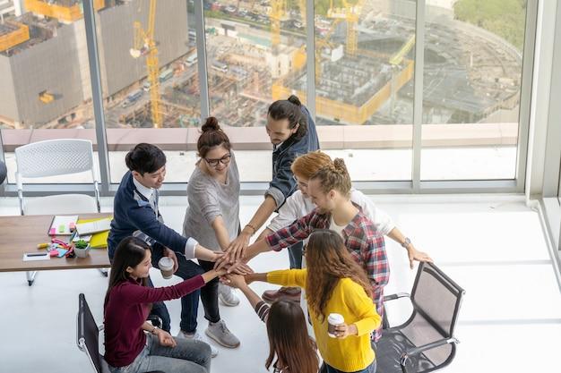 Widok z góry sceny azjatyckich i wieloetnicznych ludzi biznesu stały i koordynacja ręki