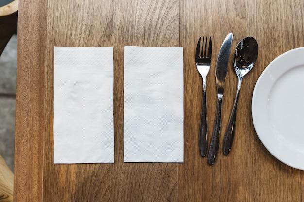 Widok z góry serwetki tkankowe i sztućce na drewnianym stole. na banner żywności.