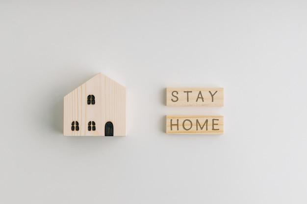 Widok z góry sformułowania pobyt domowy na drewnianych klockach oraz drewnianym domu i drewnianej zabawce. białe tło.
