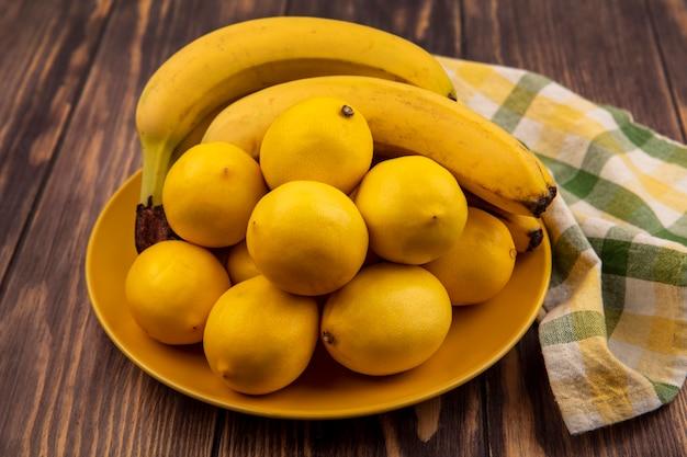 Widok z góry silnych cytryn przeciwutleniających na żółtym talerzu na szmatce w kratkę z bananami na drewnianej powierzchni