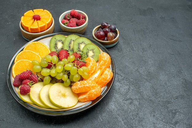 Widok z góry skład różnych owoców świeże i pokrojone owoce na ciemnym tle zdrowie dojrzałe świeże owoce łagodne