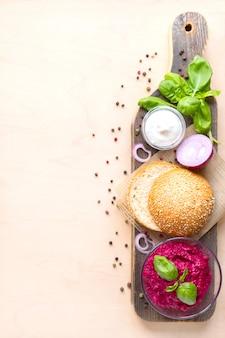Widok z góry składniki do gotowania wegańskich burgerów na jasnym drewnie