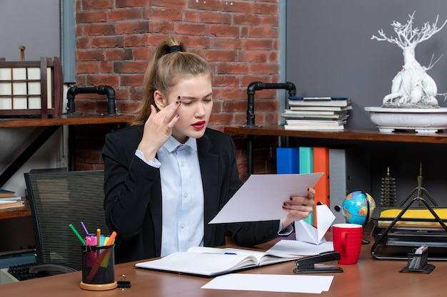 Widok z góry skoncentrowanej młodej kobiety siedzącej przy stole i trzymającej dokument, czytającej coś uważnie w biurze
