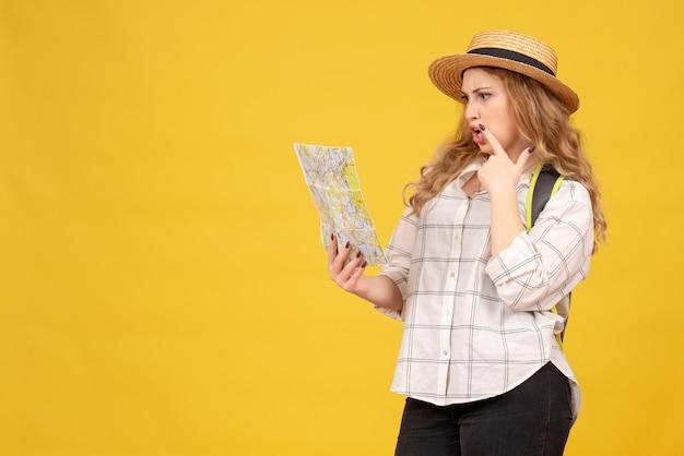 Widok z góry skupiona podróżująca dziewczyna ubrana w kapelusz i plecak patrząc na mapę na żółto