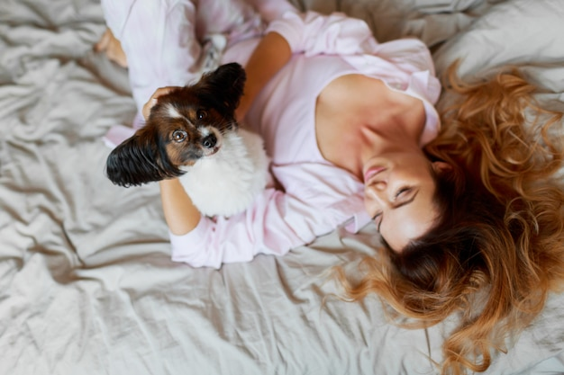 Widok z góry. śliczny figlarny szczeniak szuka i siedzi na łóżku z ładną rudą dziewczyną.