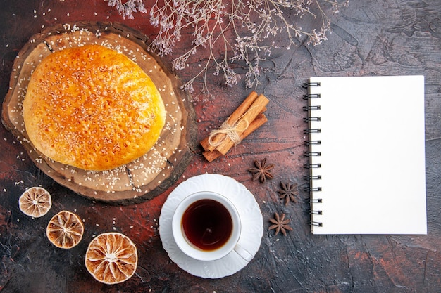 Widok z góry słodka pieczona bułka z filiżanką herbaty na ciemnej powierzchni