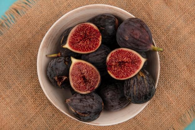 Widok z góry słodkich dojrzałych czarnych fig misyjnych na misce na worek szmatką na niebieskim tle
