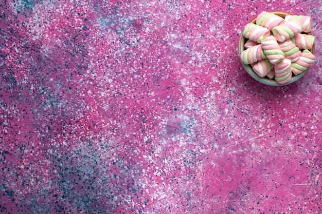Widok z góry słodkich kolorowych pianek lekko uformowanych wewnątrz okrągłej doniczki na różowej powierzchni