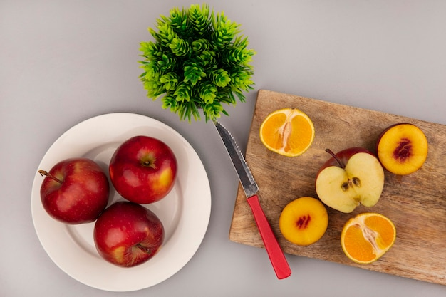 Widok z góry słodkich owoców, takich jak brzoskwinie, jabłka i mandarynki, odizolowane na drewnianej desce kuchennej z nożem z czerwonymi jabłkami na talerzu na szarej ścianie