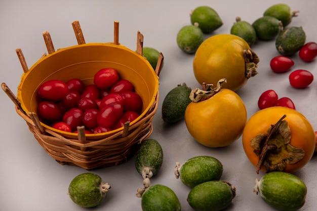 Widok z góry słodkich wiśni derenia na wiadrze z owocami feijoas i persimmon odizolowanymi na szarej ścianie
