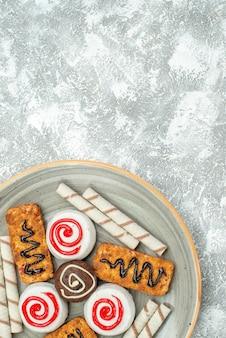 Widok z góry słodkie ciasteczka i ciasta na jasnym białym tle ciastko herbatniki herbatniki cukru ciasteczka słodkie