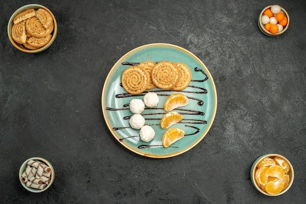 Widok z góry słodkie ciasteczka z cukierkami kokosowymi wewnątrz talerza na szarym biurku